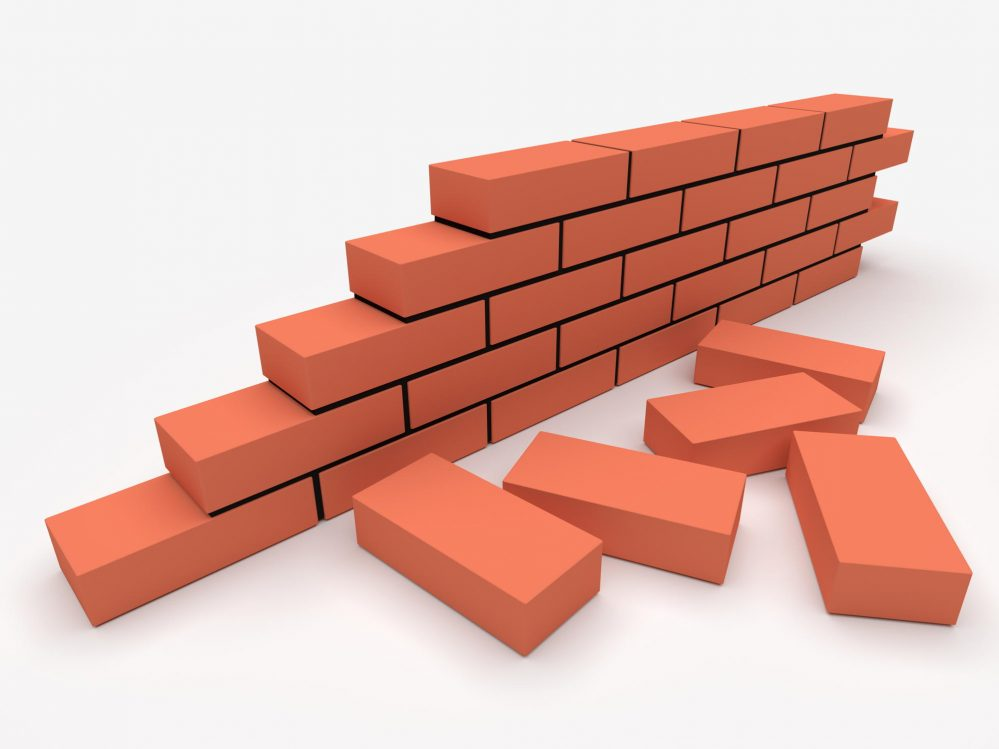 Individual bricks and partially completed brick wall