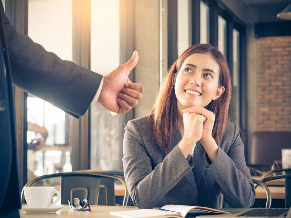 Man giving thumbs up to a woman for a job well-done
